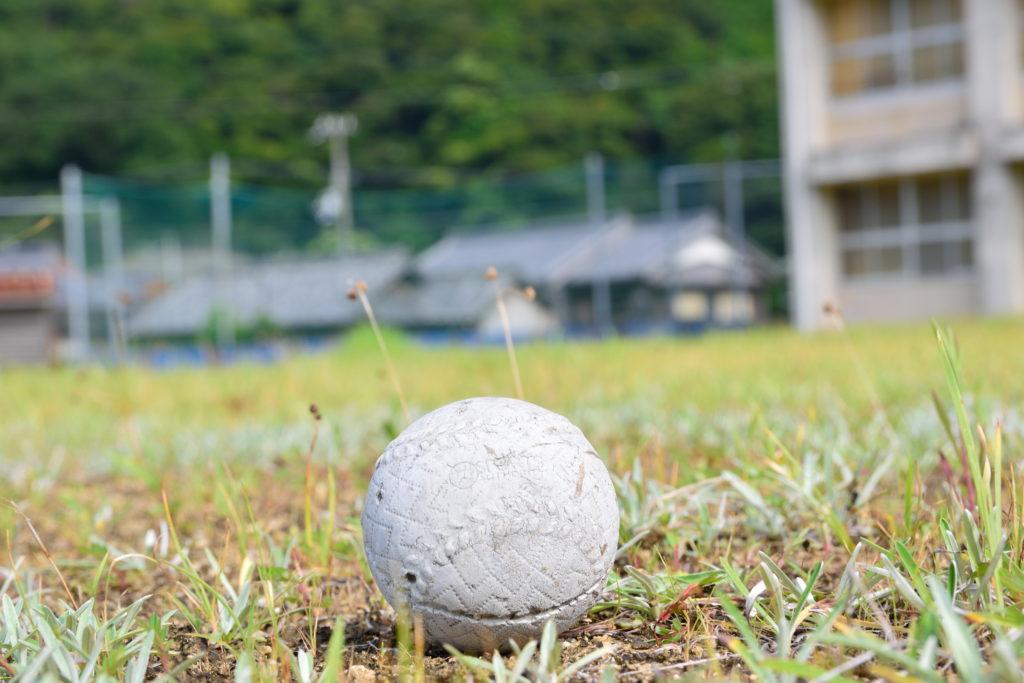 芝生に転がる風化した軟式野球ボール