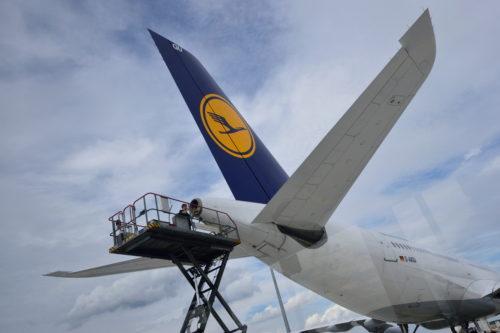 尾翼のエンジンを修理する人
